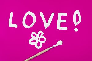 Love word with flower painted on pink