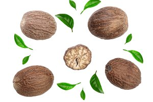 Nutmeg decorated with leaves isolated on white background. Top view