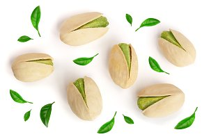 Pistachios decorated with leaves isolated on white background, top view. Flat lay