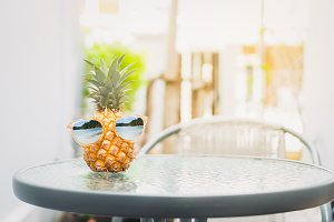 Pineapple with glasses is worn.