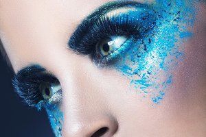 Close-up of a woman with blue makeup