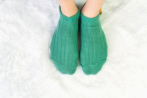 Legs in socks green colors.