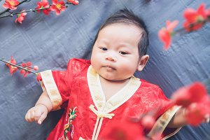 Baby in red dress on blue cloth.