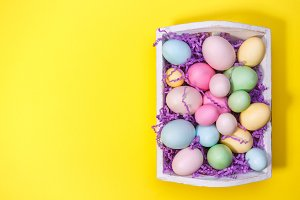 Tray with colorful eggs on yellow