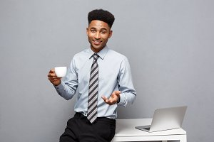 Business Concept - portrait of african american businessman having coffee sitting at a desk using a laptop