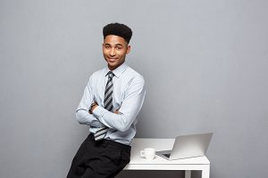 Business Concept - portrait of african american businessman talking and having coffee sitting at a desk using a laptop