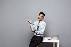 Business Concept - portrait of african american businessman with glasses having coffee sitting at a desk using a laptop.