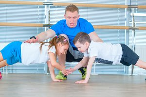Group of children doing kids gymnastics in gym with teacher. Happy sporty children in gym. bar exercise. plank.