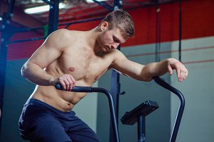 Fit young man using exercise bike at the gym. Fitness male using air bike for cardio workout at cross training gym.