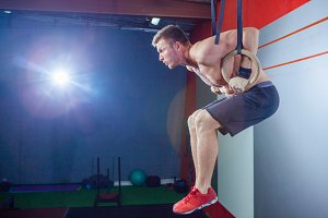 Muscle-up exercise young man doing intense cross fit workout at the gym on gymnastic rings.