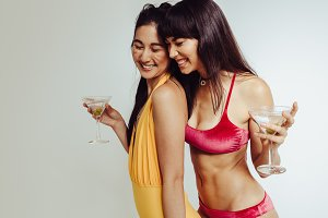 Smiling female friends with cocktail