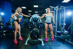 Two muscular sexy fitness woman woman relaxing in the gym. Concept of healthy lifestyle. Bodybuilder in the gym