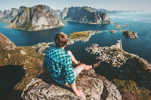 Man sitting on mountain top cliff
