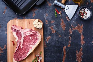 Raw T-bone steak and iron grill pan