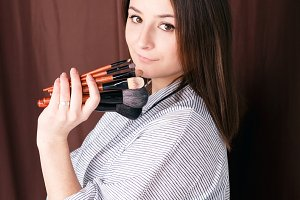 Portrait of make up artist woman with makeup brushes near face. Business portrait make up artist concept