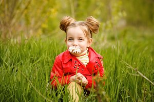 Little girl is sniffing flower