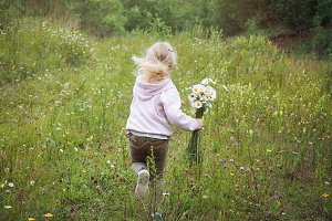 A little girl runs away. Field, green grass.