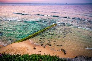 Old stone pier overgrown with algae
