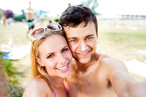 Young couple sunbathing, taking selfie. Sunscreen on the nose.