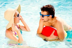 Couple with sunglasses in swimming pool. Summer, sun, water.
