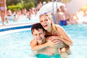 Couple in the swimming pool, piggyback. Summer, sun, water.