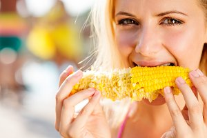 Woman in bikini eating corn. Summer and heat.