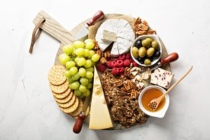 Cheese and snacks plate on white background