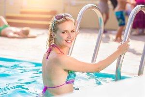 Woman in bikini standing on the pool stairs