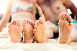 Feet of unrecognizable couple sitting on the sandy beach