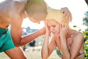 Man helping woman in bikini with heatstroke, summer heat