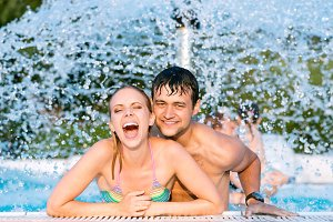 Couple in swimmning pool under splashing fountain. Summer heat.
