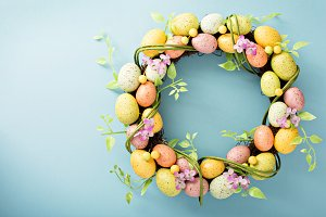 Easter eggs wreath on light blue background