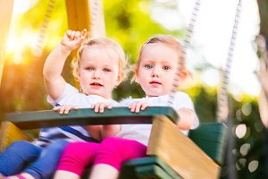 Two beautiful little girls swinging in the park.