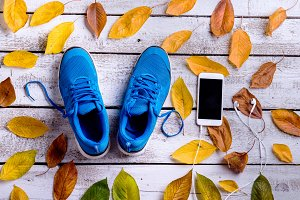 Sports shoes. Smartphone, earphones, autumn leaves. White wooden