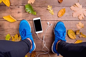 Runner in sports shoes. Smartphone and earphones. Autumn leaves.