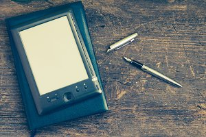 Black ereader with notebook and ink pen
