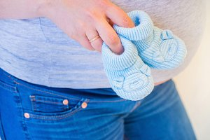 Pregnant woman holding blue baby booties