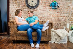 Beautiful pregnant woman and man sitting near wall