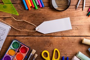 Desk, school supplies, empty tag, wooden background, copy space