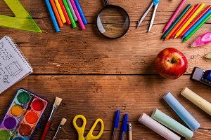 Desk with school supplies against wooden background, copy space
