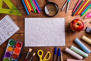 Desk, school supplies, empty paper, wooden background, copy spac
