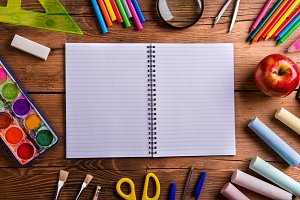 Desk, school supplies, lined paper, wooden background, copy spac