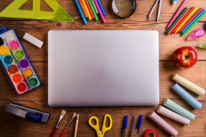 Desk, school supplies, closed notebook, wooden background, copy