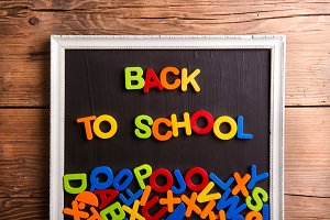Colorful plastic letters in picture frame, back to school,