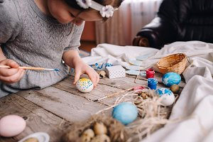 Child girl painting Easter eggs