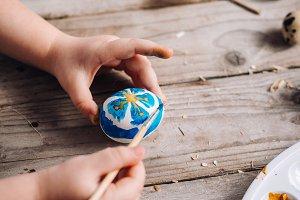 Child girl painting Easter eggs