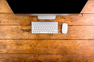 Computer, keyboard and mouse layid on wooden office desk