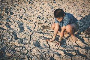 Sad boy sitting on cracked ground