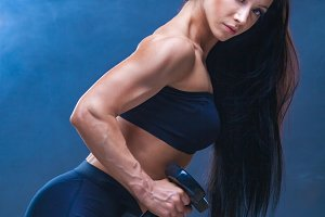 athletic young woman doing a fitness workout with dumbbells on black studio background. Around the shrouds the model smoke.
