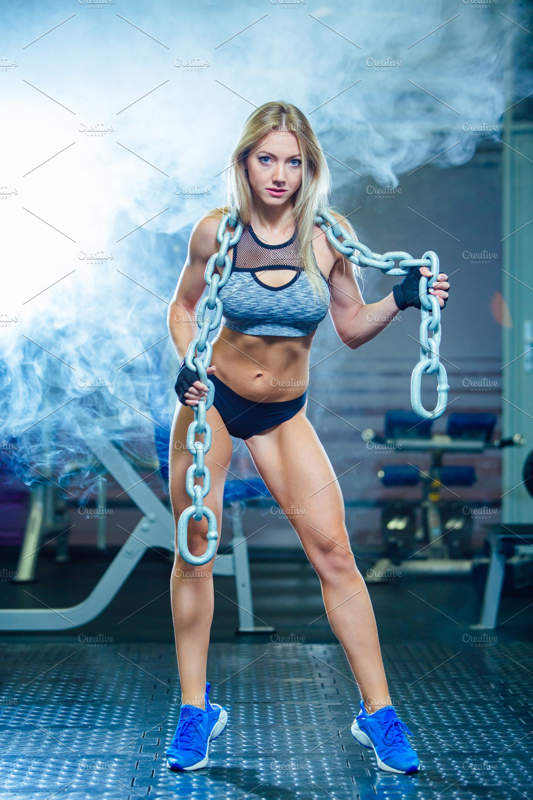 Young sexy woman doing exercises with heavy chain in gym  Classic  bodybuilding  Muscular blonde fitness woman doing exercises in the gym   Fitness